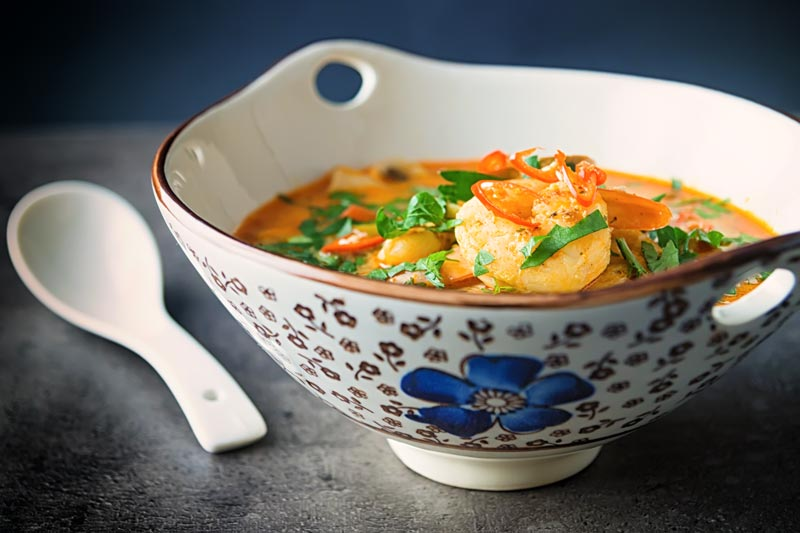 Landscape image of a Tom Yum Soup served in an Asian style soup bowl decorated with a blue flower in a dark setting