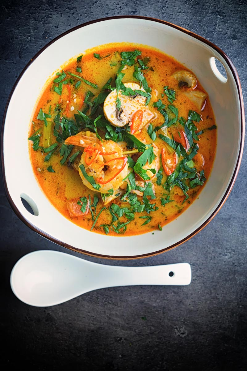 Portrait overhead image of a Tom Yum Soup served in an Asian style soup bowl decorated with a blue flower in a dark setting