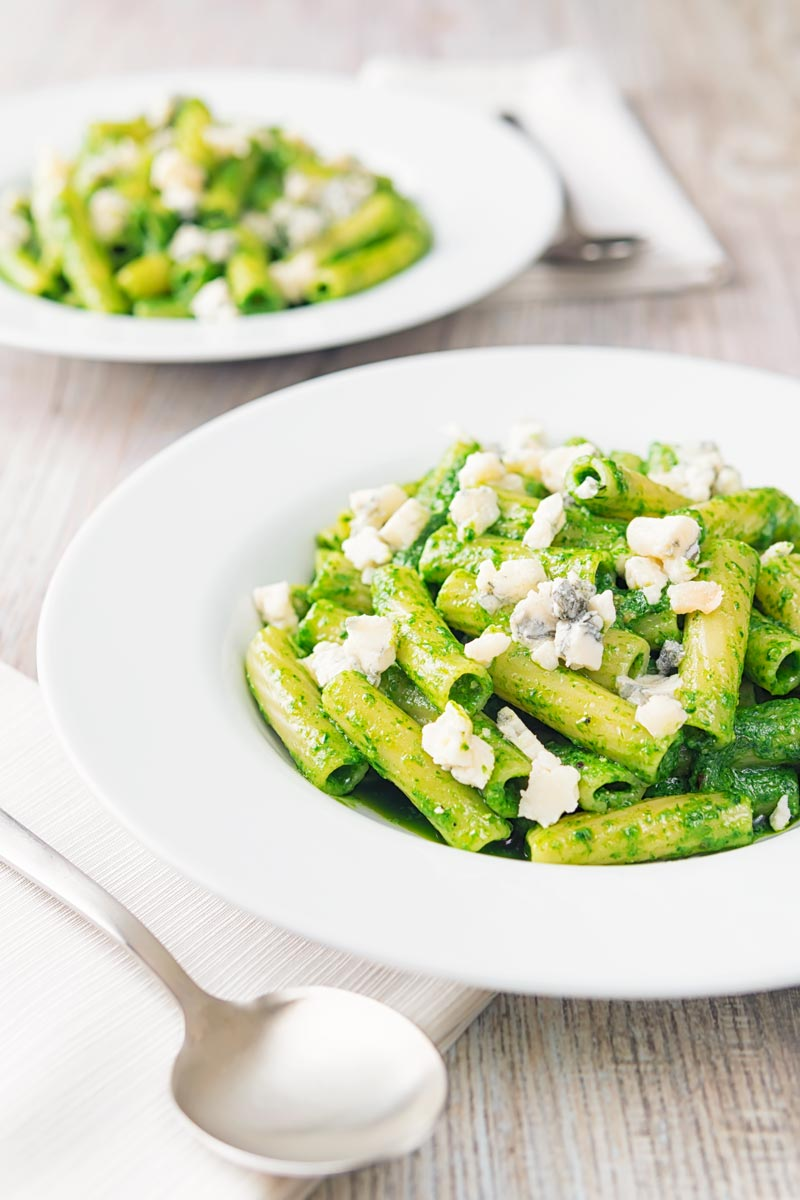 Portrait image of wild garlic pesto pasta using rigatoni pasta garnished with gorgonzola cheese served in two wide white bowls