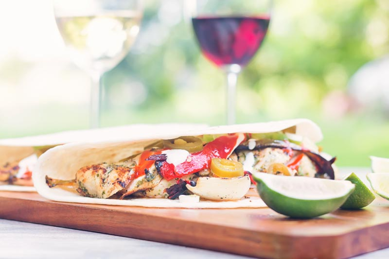 Landscape image of BBQ Chicken Fajitas with a lime wedge in an outdoor setting featuring two glasses of wine