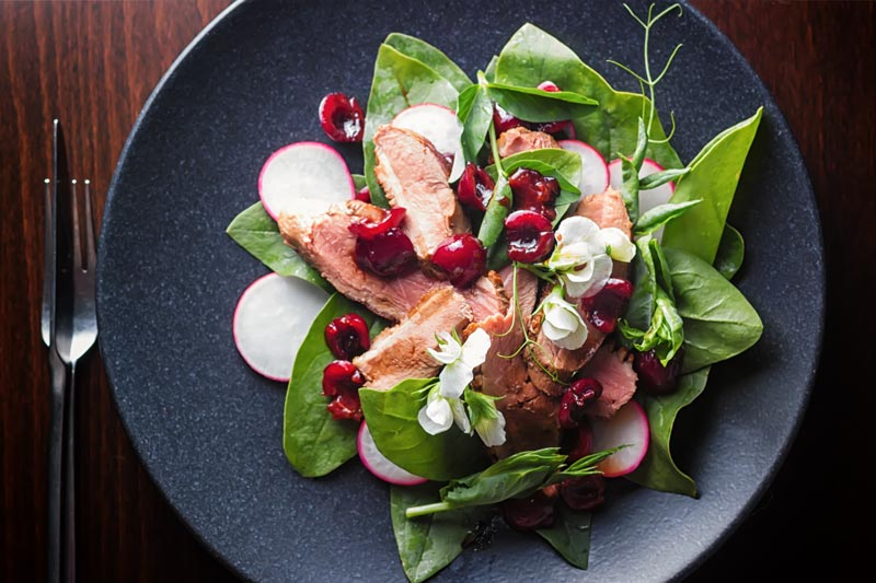 Landscape overhead image of a duck salad featuring sliced pan fried duck breast, Balsamic cherries, Spinach and Radish served on a black plate