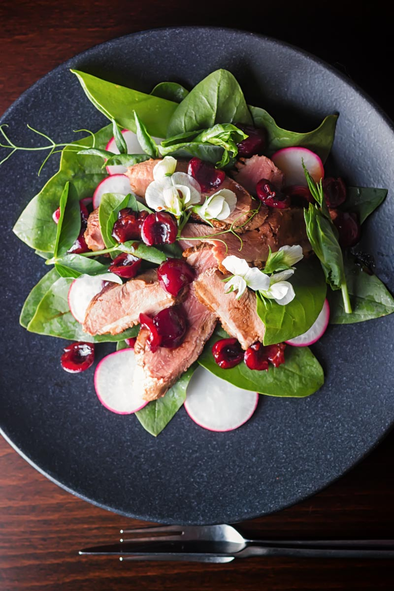 Portrait overhead image of a duck salad featuring sliced pan fried duck breast, Balsamic cherries, Spinach and Radish served on a black plate