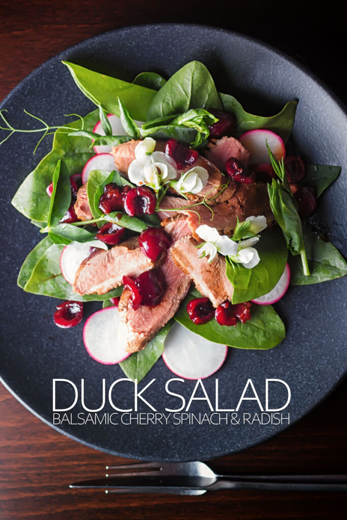 Portrait overhead image of a duck salad featuring sliced pan fried duck breast, Balsamic cherries, Spinach and Radish served on a black plate with text