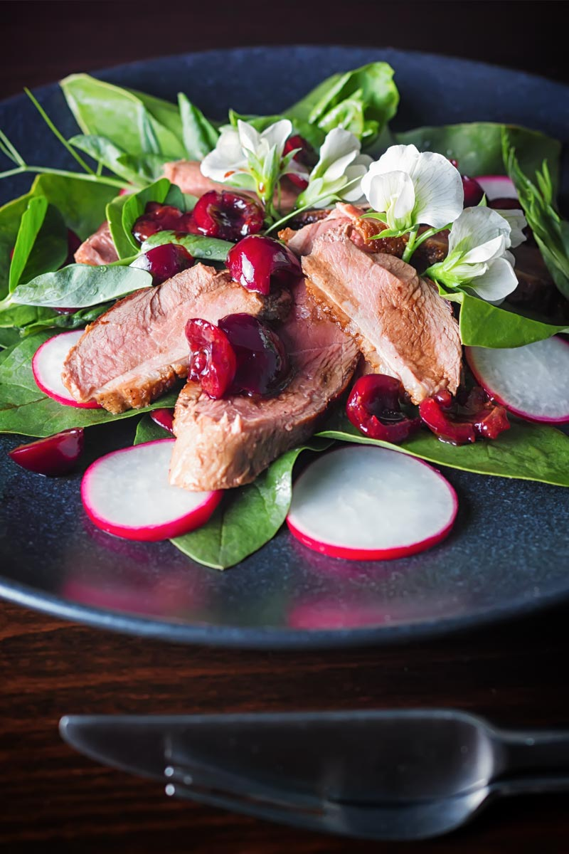 Portrait image of a duck salad featuring sliced pan fried duck breast, Balsamic cherries, Spinach and Radish served on a black plate