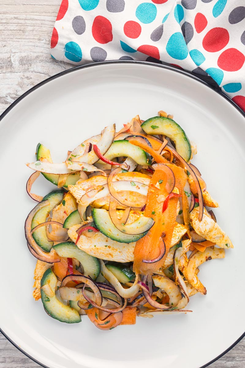 Overhead portrait image of a Thai salad featuring chicken breast, fresh coconut, carrots and red onion