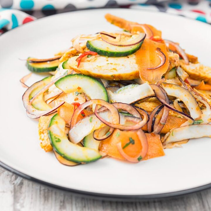 Square image of a Thai salad featuring chicken breast, fresh coconut, carrots and red onion