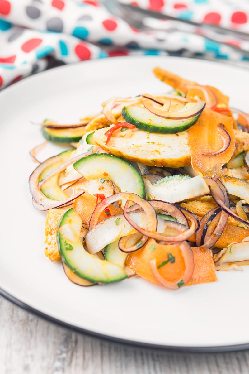 Portrait image of a Thai salad featuring chicken breast, fresh coconut, carrots and red onion