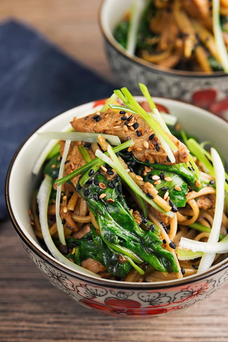 Portrait overhead image of a pork stir fry with spinach and noodles served an Asian style bowl