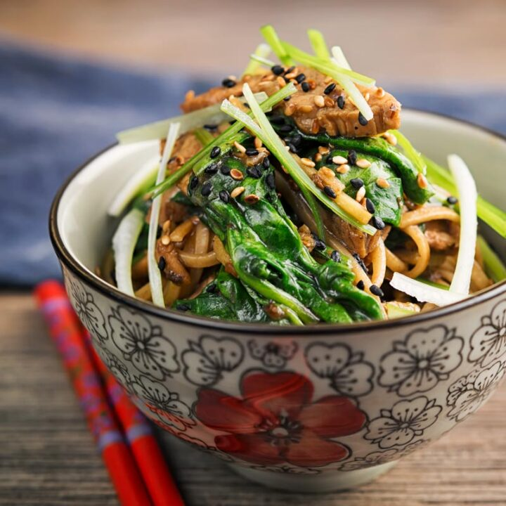 Portrait image of a pork stir fry with spinach and noodles served an Asian style bowl decorated with a red flower