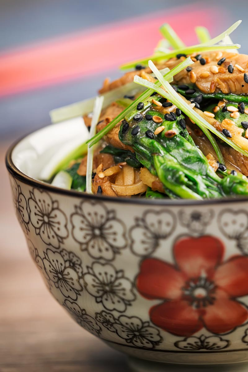 Portrait close up image of a pork stir fry with spinach and noodles served an Asian style bowl decorated with a red flower