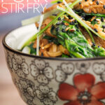 Portrait close up image of a pork stir fry with spinach and noodles served an Asian style bowl decorated with a red flower with text