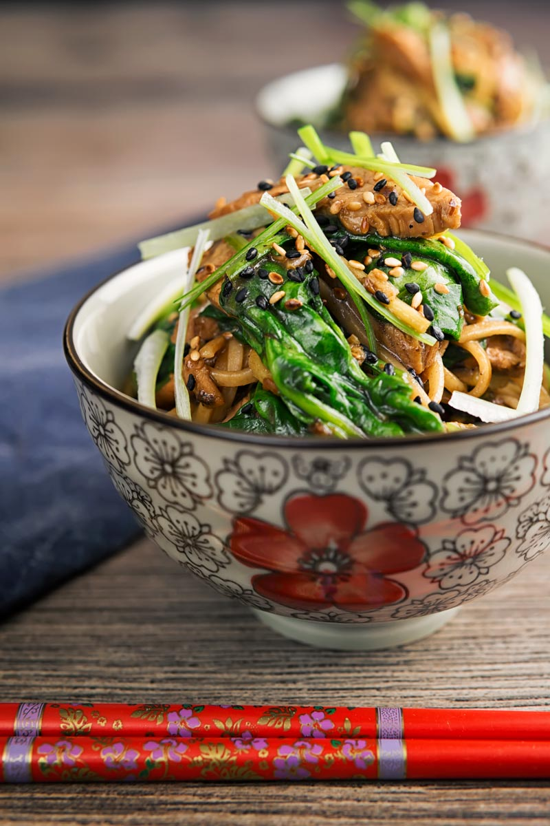 Square image of a pork stir fry with spinach and noodles served an Asian style bowl decorated with a red flower