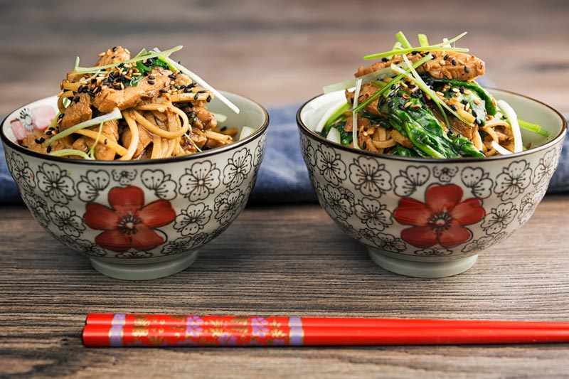 Landscape image of a pork stir fry with spinach and noodles served in two Asian style bowls decorated with a red flower
