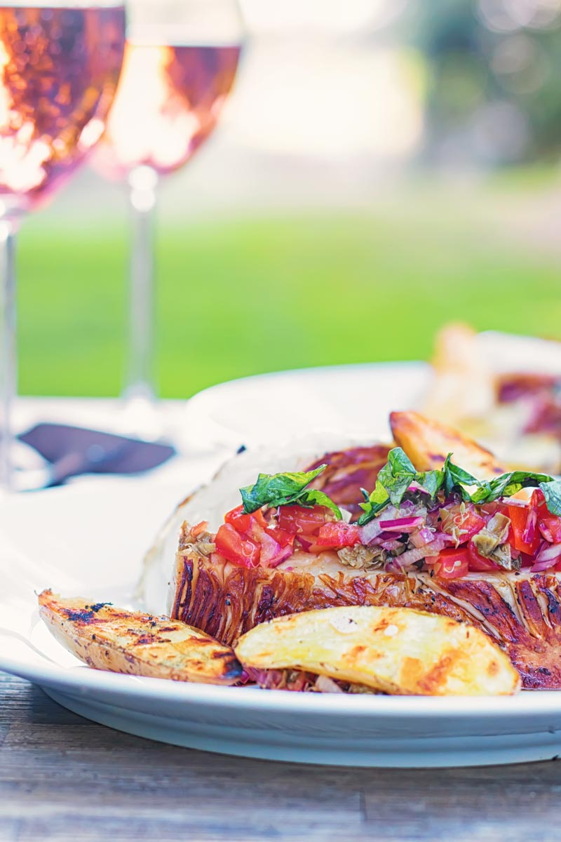 Portrait image of grilled balsamic cabbage steaks served with a tomato salsa and seared potatoes on a white plate adn two glasses of wine in a garden setting