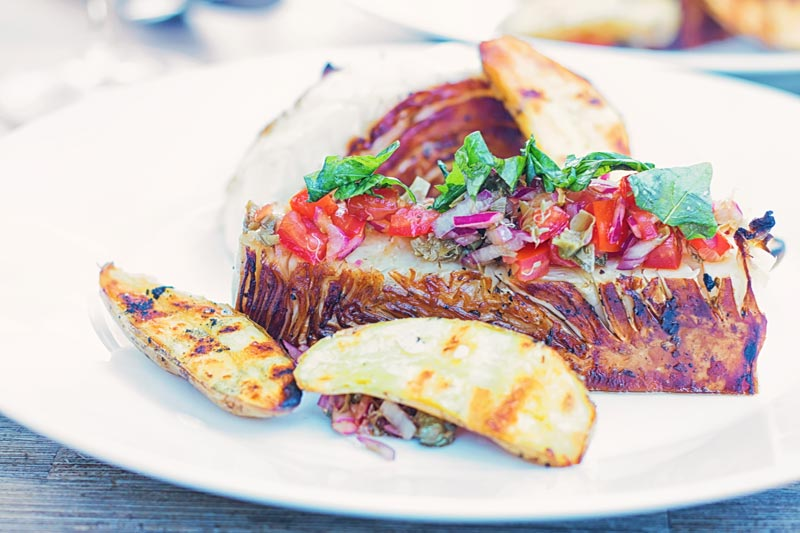 Landscape image of grilled balsamic cabbage steaks served with a tomato salsa and seared potatoes on a white plate