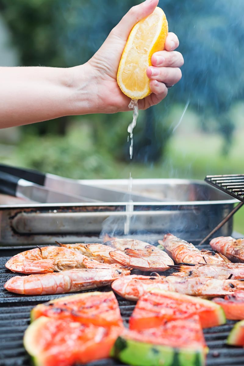 Portrait image of fresh lemon being squeezed over BBQ prawns or shrimp on a BBQ with watermelon