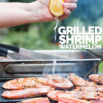 Portrait image of fresh lemon being squeezed over BBQ prawns or shrimp on a BBQ with watermelon with text