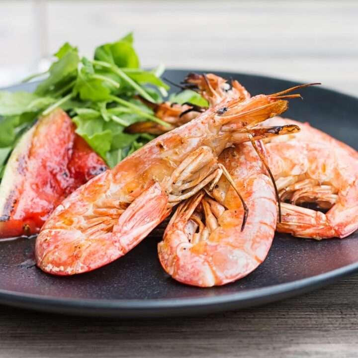 Square image of large BBQ prawns or shrimp with grilled watermelon served on a black plate