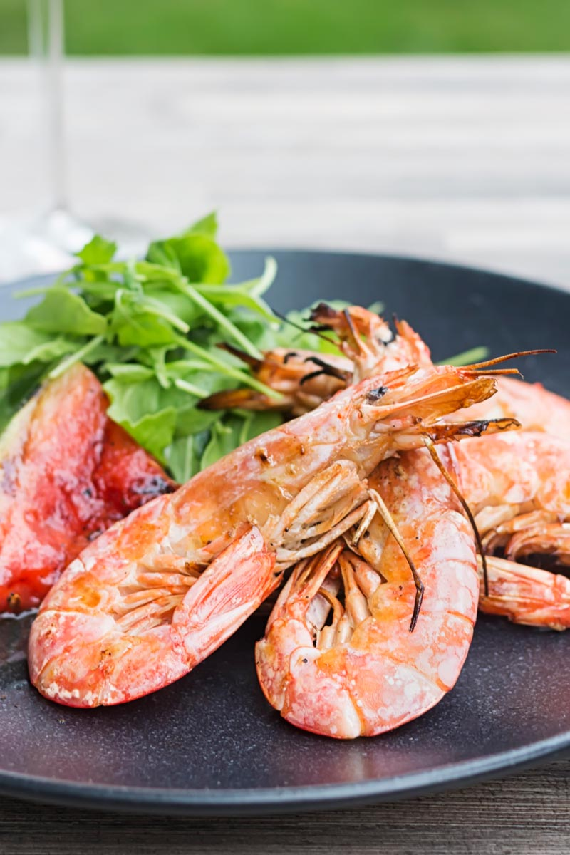 Portrait image of large BBQ prawns or shrimp with grilled watermelon served on a black plate