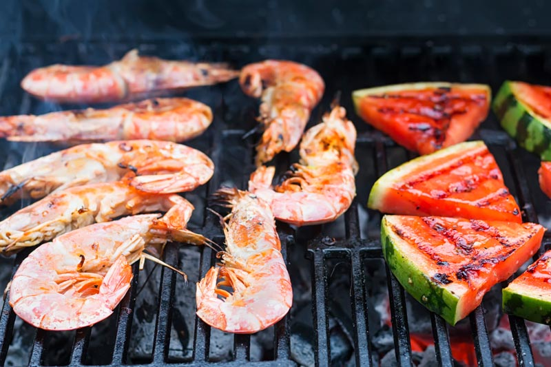 Landscape image of large BBQ prawns or shrimp with grilled watermelon being cooked on the grill