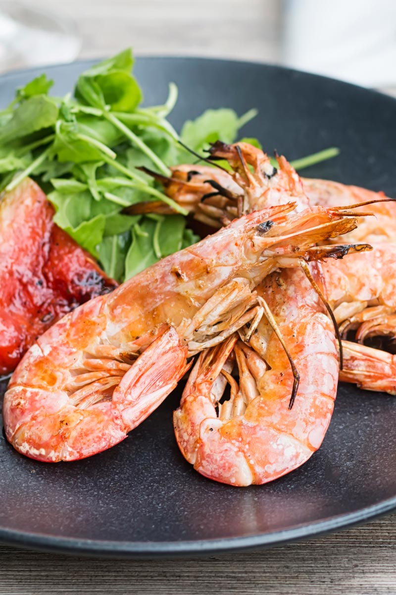 Portrait close up image of large BBQ prawns or shrimp with grilled watermelon served on a black plate