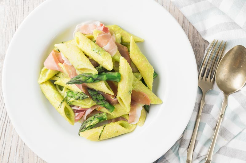 Landscape image of penne asparagus pasta with asparagus spears and Parma ham in a white bowl with vintage cutlery