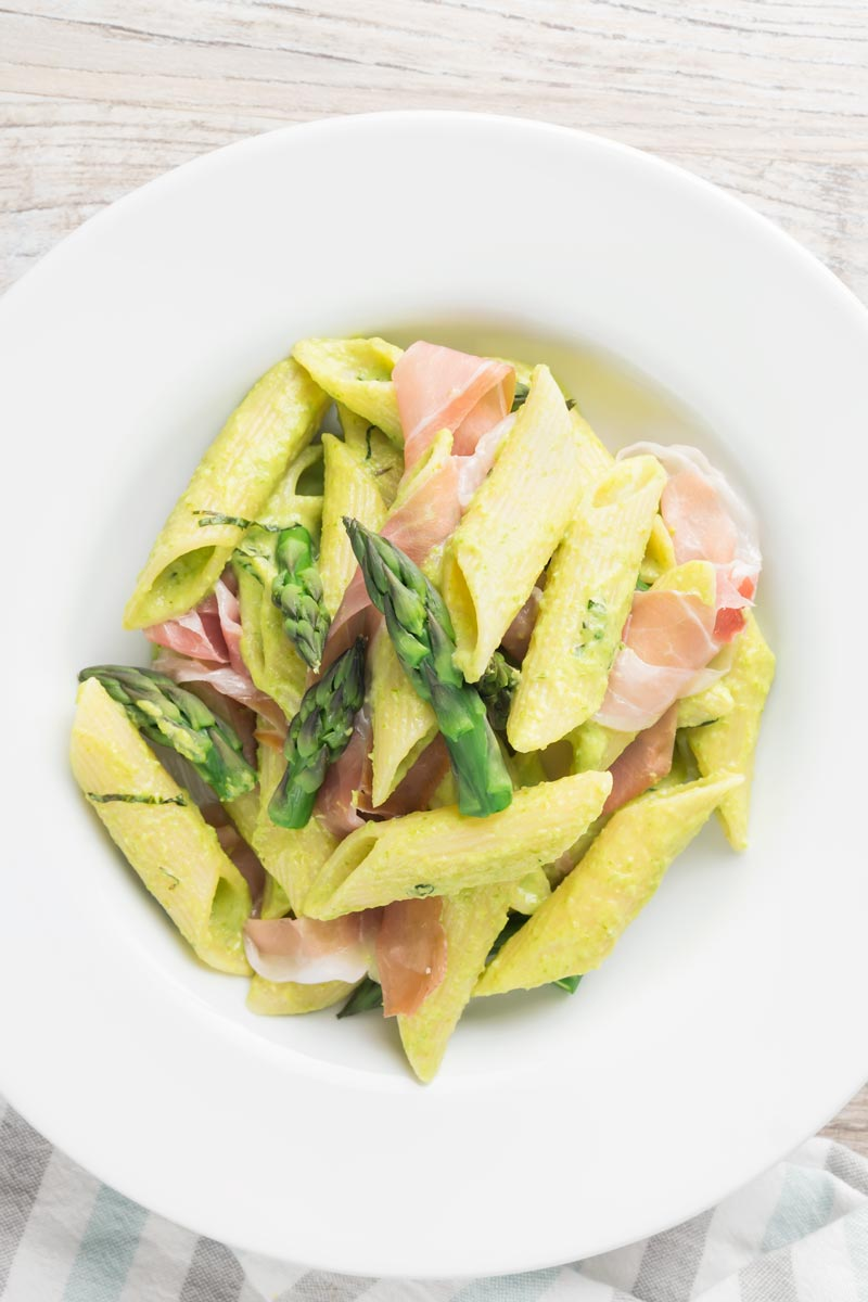 Portrait overhead image of penne asparagus pasta with asparagus spears and Parma ham in a white bowl