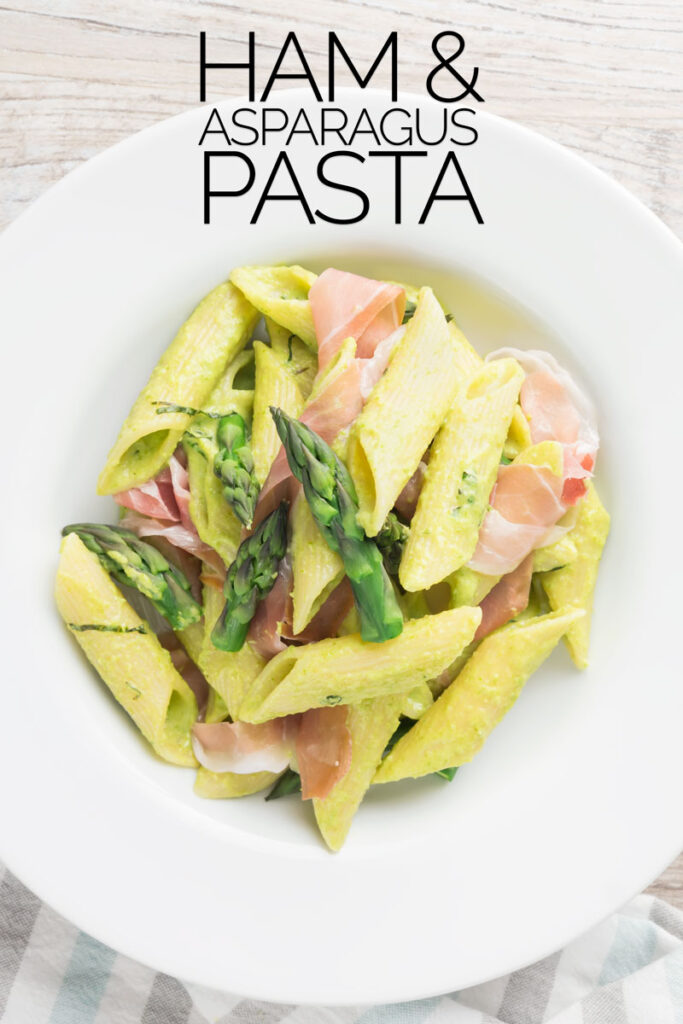 Portrait overhead image of penne asparagus pasta with asparagus spears and Parma ham in a white bowl with vintage cutlery with text