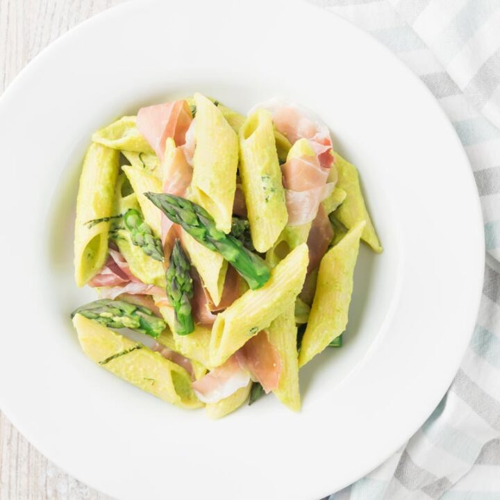 Square overhead image of penne asparagus pasta with asparagus spears and Parma ham in a white bowl with vintage cutlery