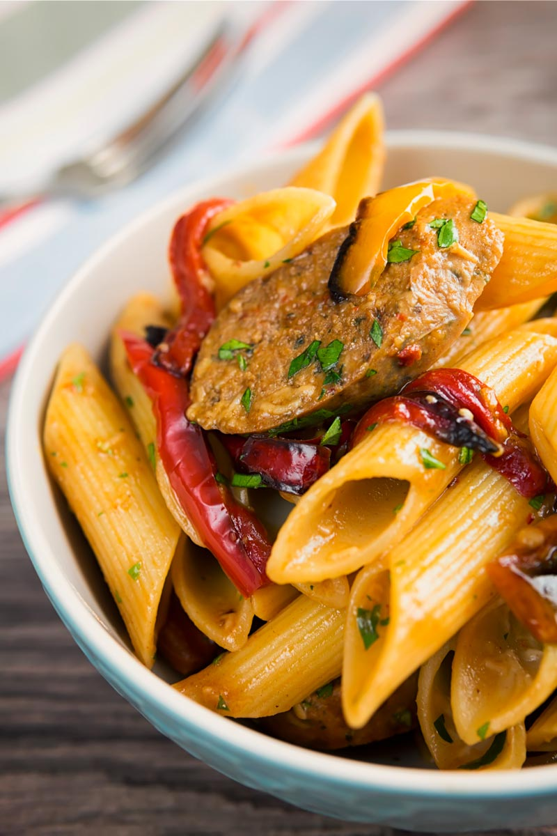 Portrait overhead image of an Italian Sausage pasta with roasted peppers and penne pasta