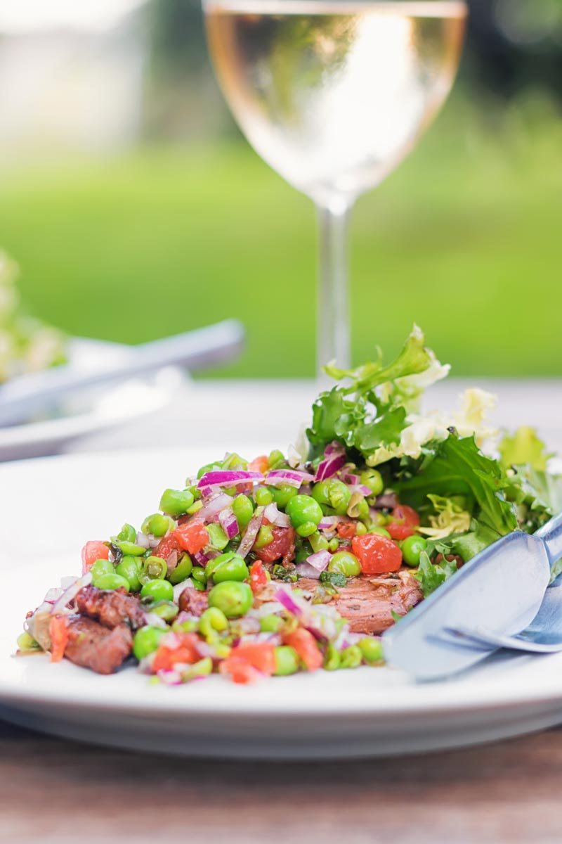 Portrait image of a minted pea salsa served with lamb and a side salad on a white plate in a garden setting with a glass of wine.