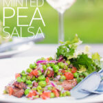 Portrait image of a minted pea salsa served with lamb and a side salad on a white plate in a garden setting with a glass of wine with text