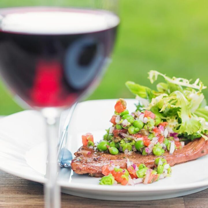 Square image of a minted pea salsa served with lamb and a side salad on a white plate in a garden setting with a glass of wine.