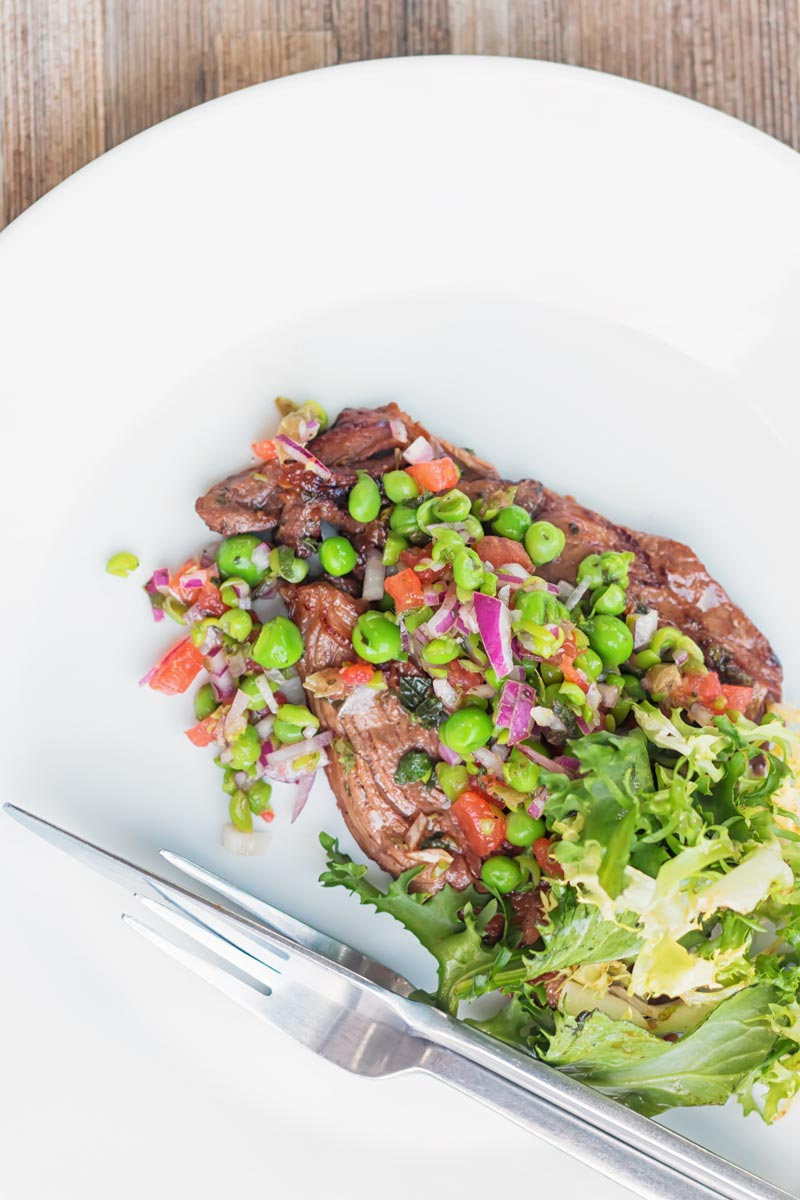 Portrait overhead image of a minted pea salsa served with lamb and a side salad on a white plate