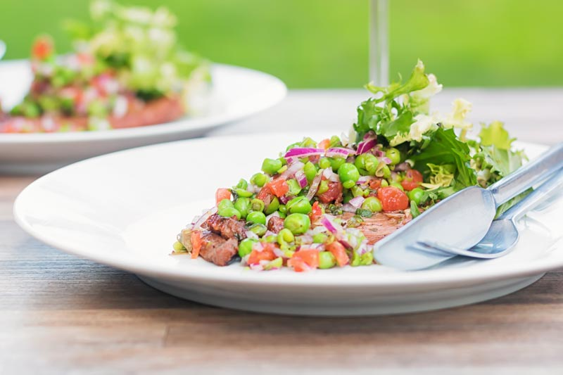 Landscape image of a minted pea salsa served with lamb and a side salad on a white plate in a garden setting