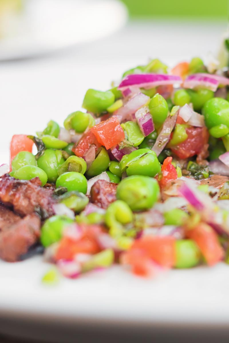 Close up portrait image of a minted pea salsa served with lamb and a side salad on a white plate
