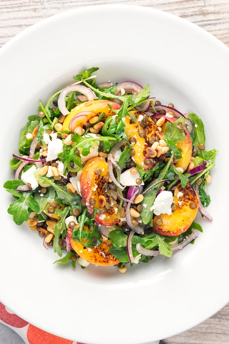 Portrait overhead image of a seared peach and feta cheese salad with rocket, puy lentils and toasted pine nuts served in a white bowl