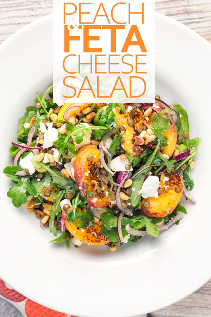 Portrait overhead image of a seared peach and feta cheese salad with rocket, puy lentils and toasted pine nuts served in a white bowl with text