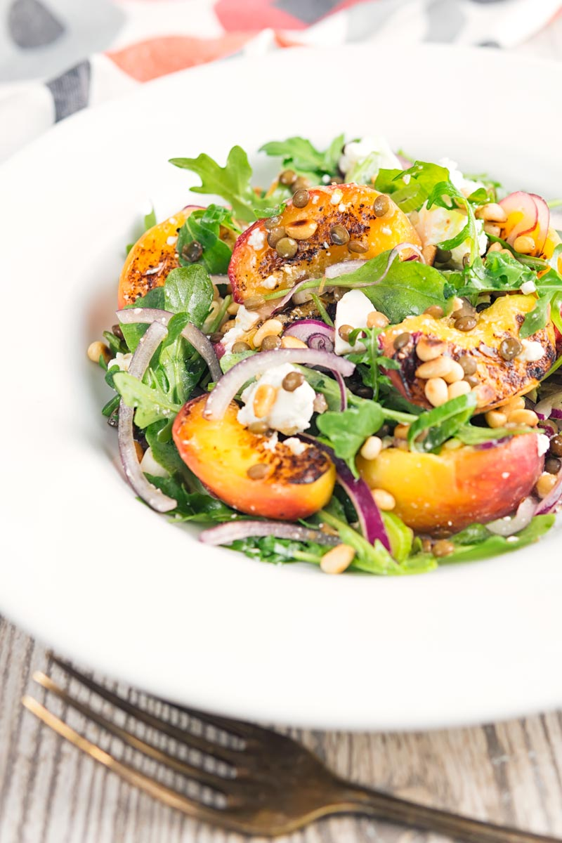 Portrait image of a seared peach and feta cheese salad with rocket, puy lentils and toasted pine nuts served in a white bowl