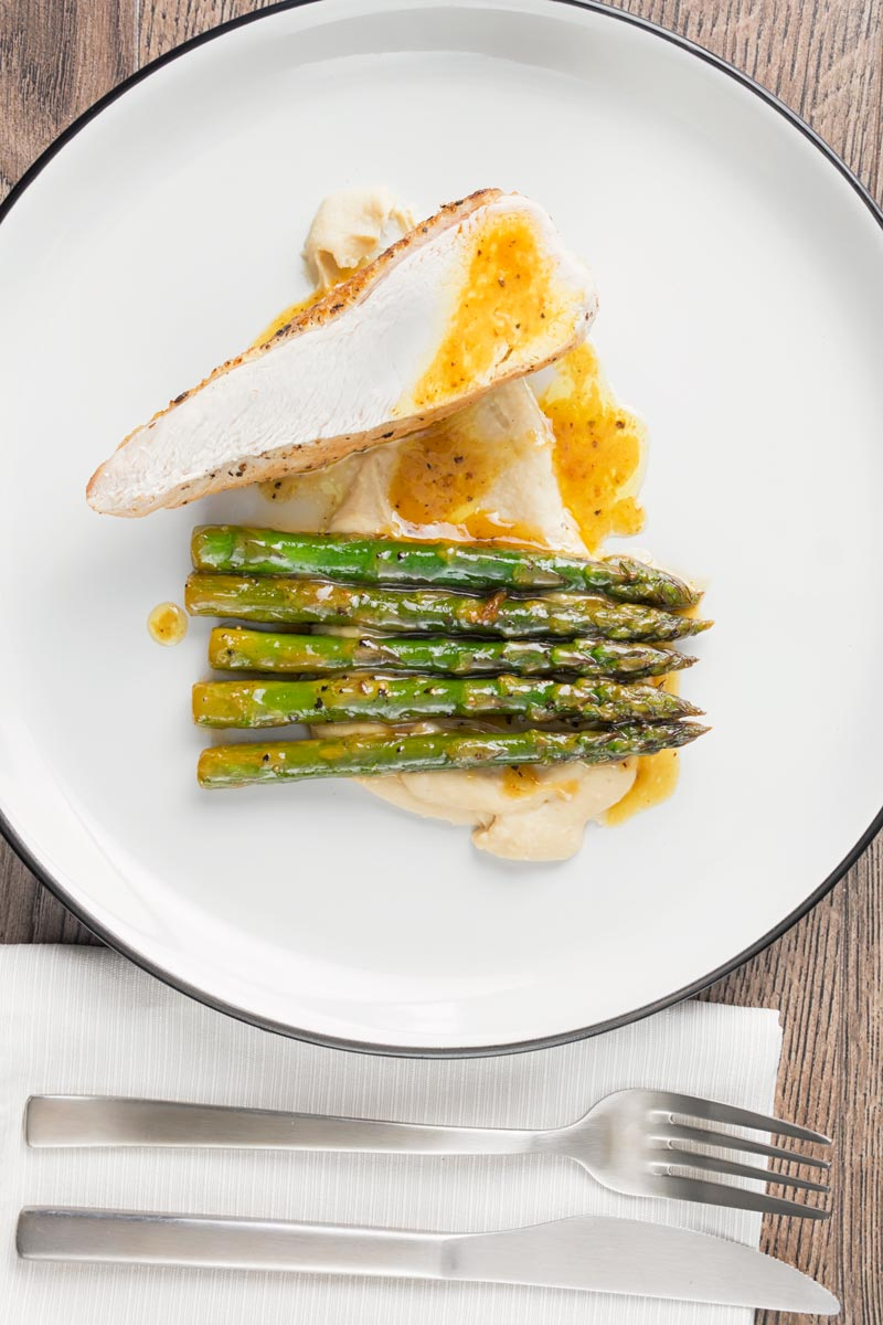 Portrait overhead image of a roast chicken breast served with white bean puree and orange asparagus served on a white plate with a black rim
