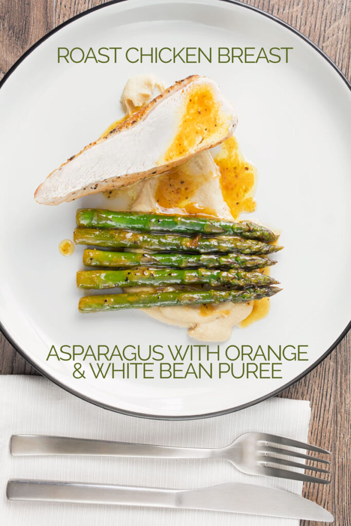 Portrait overhead image of a roast chicken breast served with white bean puree and orange asparagus served on a white plate with a black rim with text