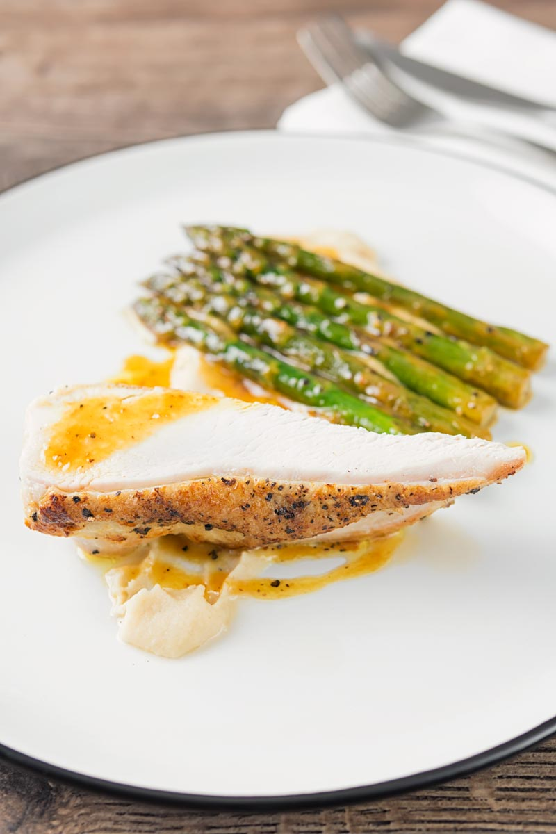 Portrait image of a roast chicken breast served with white bean puree and orange asparagus served on a white plate with a black rim