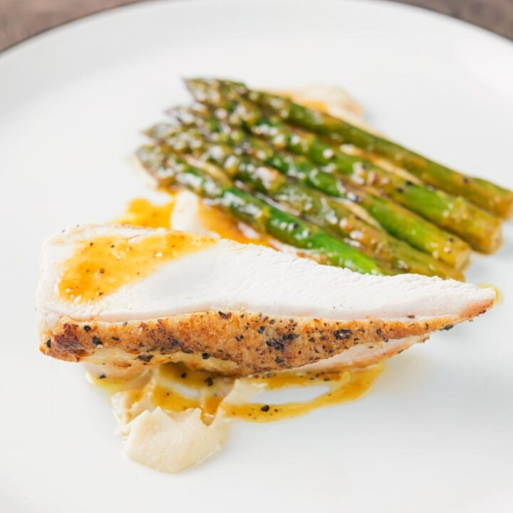 Sqaure image of a roast chicken breast served with white bean puree and orange asparagus served on a white plate with a black rim
