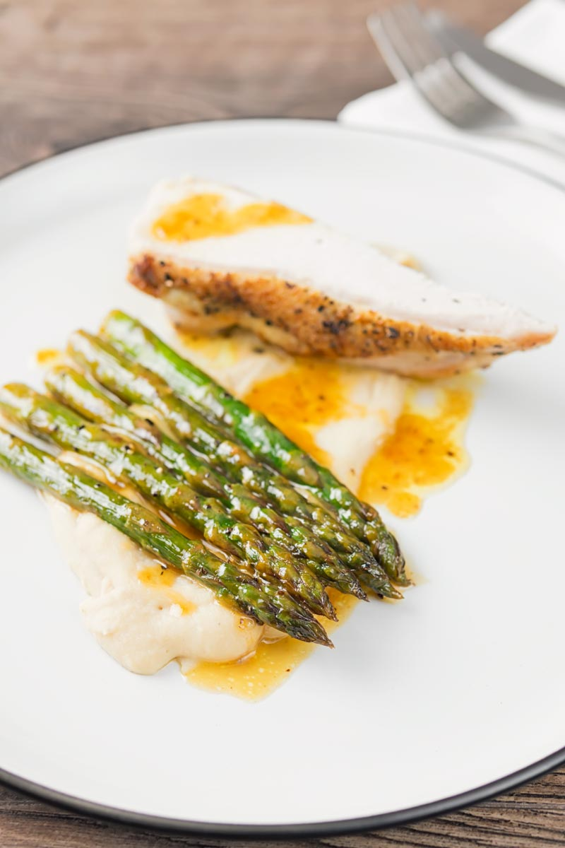Portrait image of orange asparagus served with white bean puree and a roast chicken breast served on a white plate with a black rim