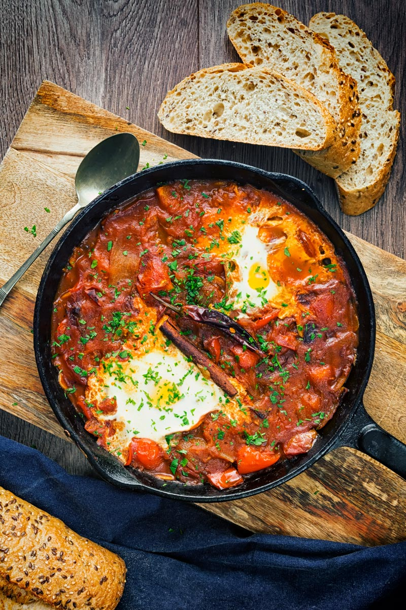 Portrait overhead image of Shakshouka served in a cast iron skillet featuring baked eggs served with wholegrain bread