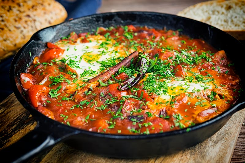 Landscape image of Shakshouka served in a cast iron skillet featuring baked eggs served with wholegrain bread