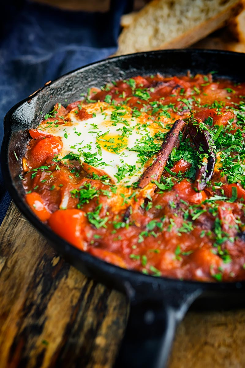Portrait image of Shakshouka served in a cast iron skillet featuring baked eggs served with wholegrain bread