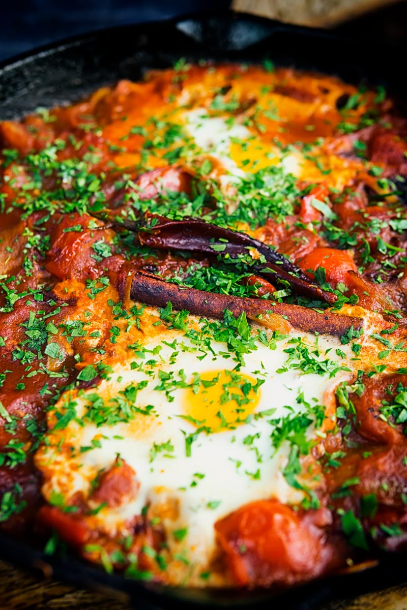 Portrait close up image of Shakshouka served in a cast iron skillet featuring baked eggs served with wholegrain bread