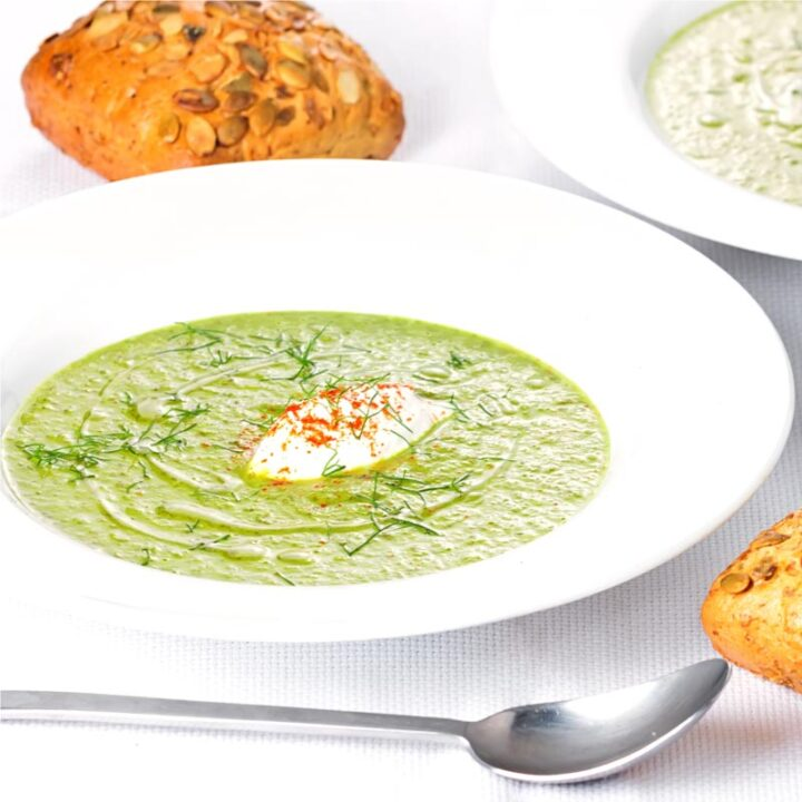 Square image of a sorrel and fennel soup served in a white bowl with a dollop of sour cream and sprinkling of paprika