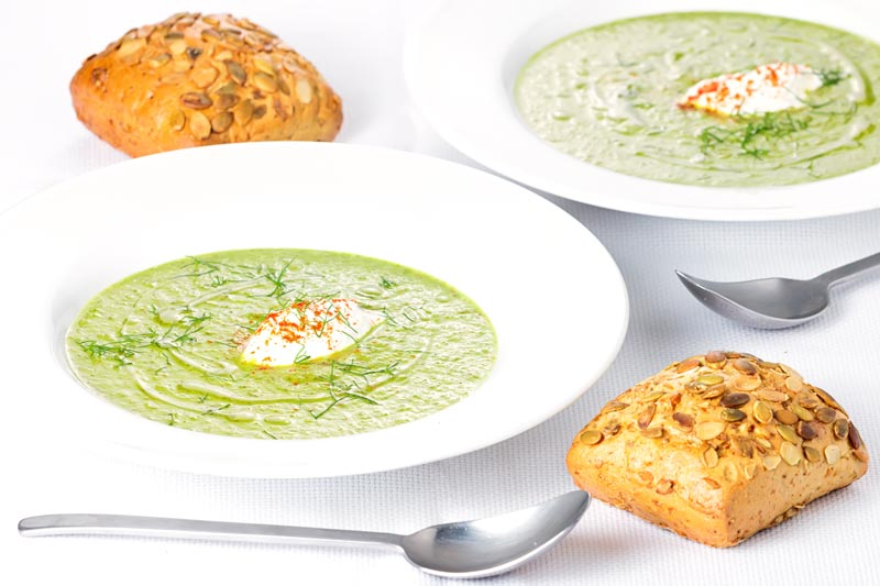Landscape image of two bowls of sorrel and fennel soup served in a white bowl with a dollop of sour cream and sprinkling of paprika